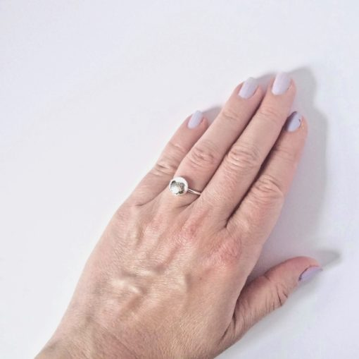 Round pebble silver ring worn on fourth finger left hand - on white background