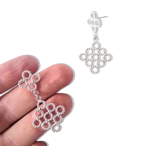Silver Beaded Quatrefoil Dangle Earrings - one earring held on palm of hand, other earring on white background nearby