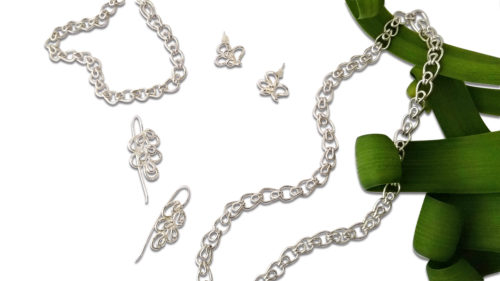 Leaves range - silver jewellery on white background with green foliage