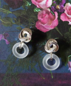 Graphic Rose Dangle Earrings - Silver and Frosted Rock Crystal - on floral background