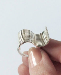 Silver Wave Ring - held between index and thumb - on white background